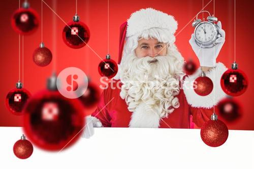 Composite image of santa claus holding alarm clock and sign