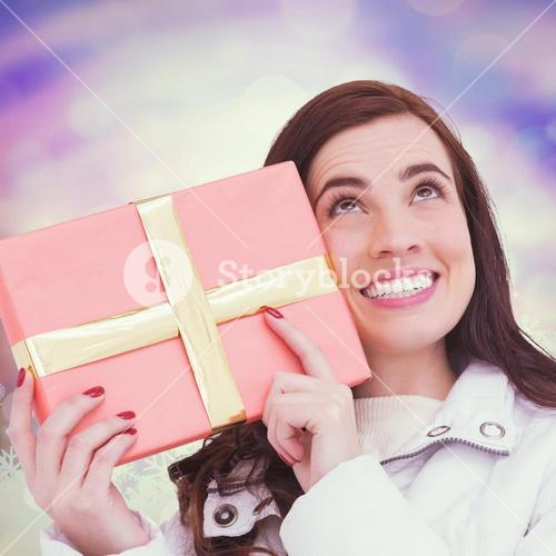 Composite image of portrait of a happy brunette holding gift