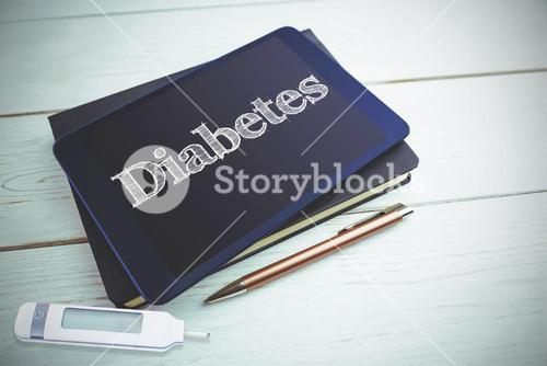 Diabetes against view of a book and tablet lying on desk