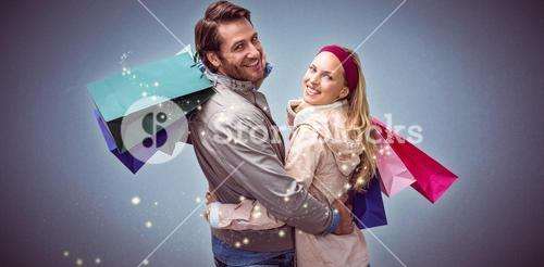 Composite image of smiling couple with shopping bags embracing