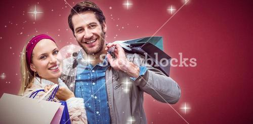 Composite image of smiling couple with shopping bags