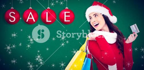 Composite image of festive brunette holding shopping bags and credit card