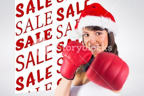 Composite image of festive brunette punching with boxing gloves
