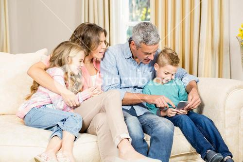 Happy family using phone on sofa