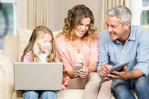 Happy family using laptop, tablet and smartphone
