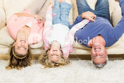 Parents and child upside down on the couch