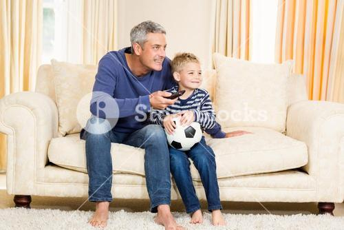 Father and son watching football match on tv