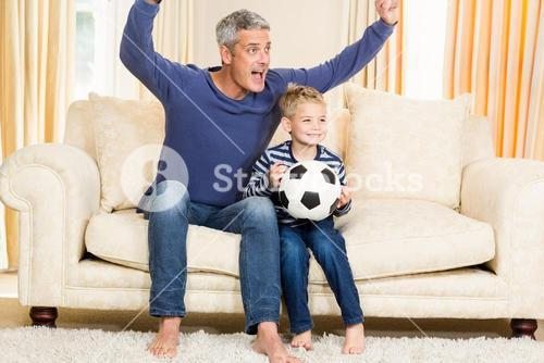 Father and son exulting on the sofa