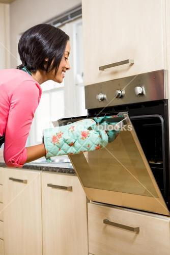 Smiling woman looking in the oven