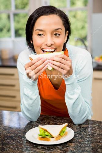 Day dreaming brunette eating sandwich