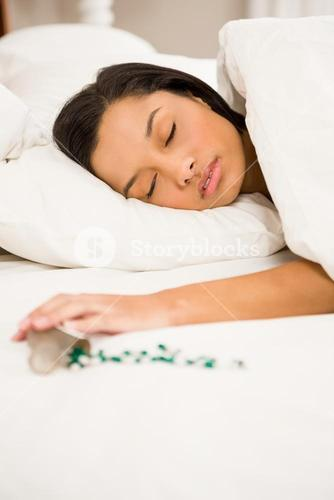 Brunette sleeping in bed by spilt bottle of pills