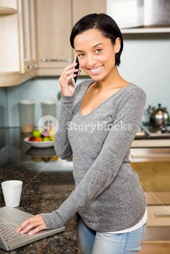 Smiling brunette on a phone call using laptop