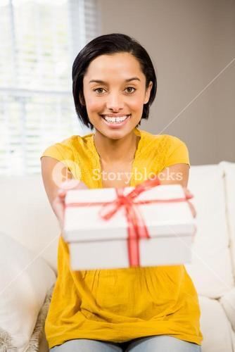 Smiling brunette holding gift to the camera