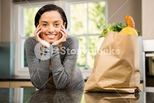 Smiling brunette with  grocery bag on counter