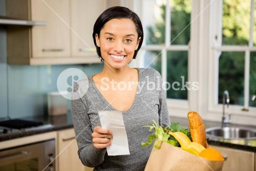 Smiling brunette holding receipt in kitchen