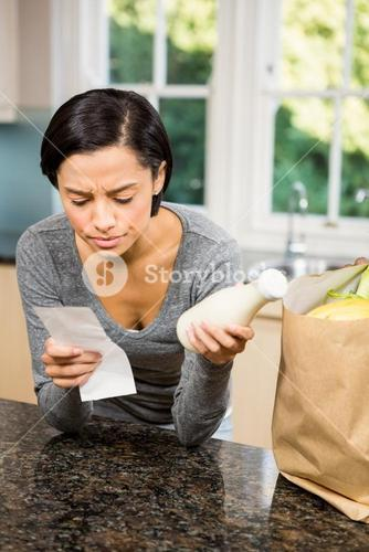 Frowning brunette holding receipt and milk