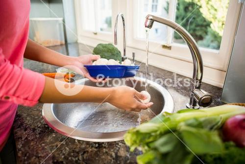 Mid section of woman washing mushrooms