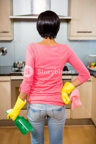Rear view of standing brunette ready to clean the kitchen