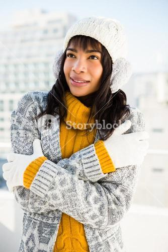 Smiling woman wearing winter clothes with arms crossed