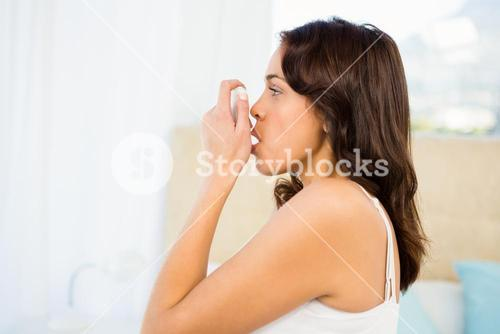 Side view of a woman using her inhaler