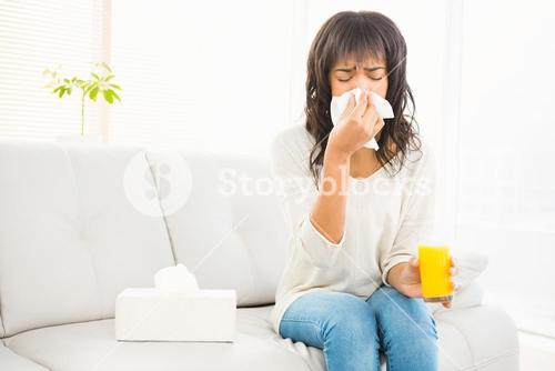 Pretty woman sneezing on couch