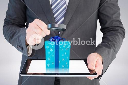 Composite image of businessman looking at tablet with magnifying glass