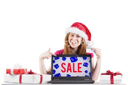 Composite image of festive redhead shopping online with laptop
