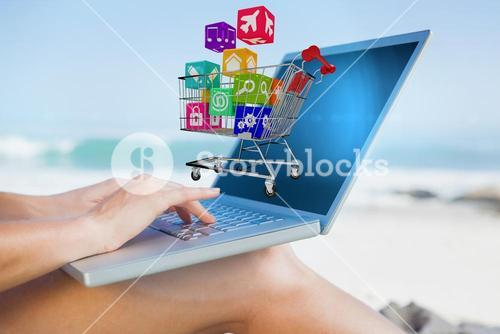 Composite image of woman sitting on beach using her laptop