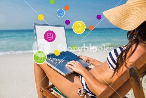 Composite image of pretty brunette using laptop on deck chair