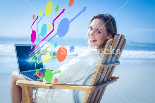 Composite image of gorgeous blonde sitting on deck chair using laptop on beach