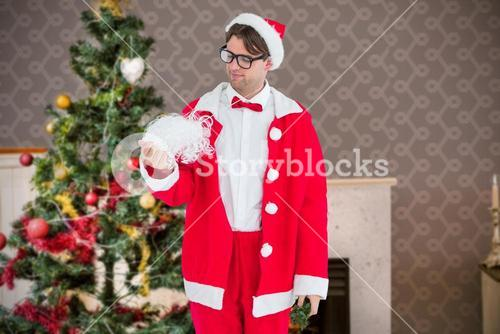 Composite image of geeky hipster in santa costume looking at beard