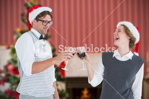 Composite image of happy geeky hipster couple drinking red wine