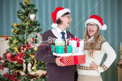 Composite image of geeky hipster couple holding presents