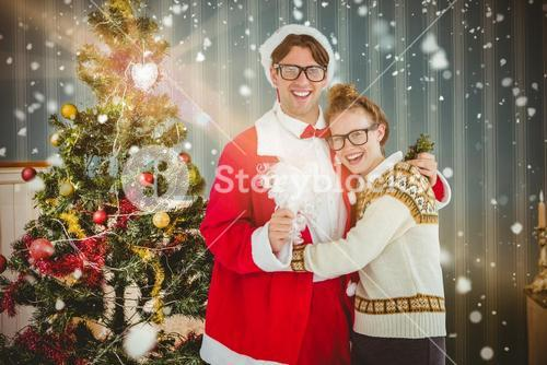 Composite image of geeky hipster in santa costume hugging his girlfriend