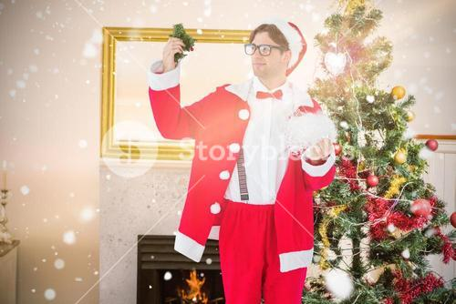Composite image of geeky hipster in santa costume looking at mistletoe