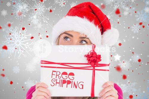 Composite image of festive blonde holding christmas gift