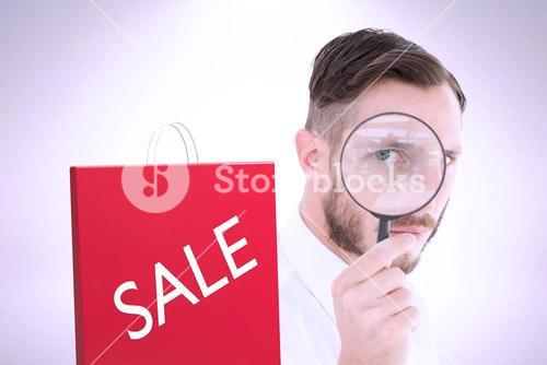 Composite image of geeky businessman looking through magnifying glass