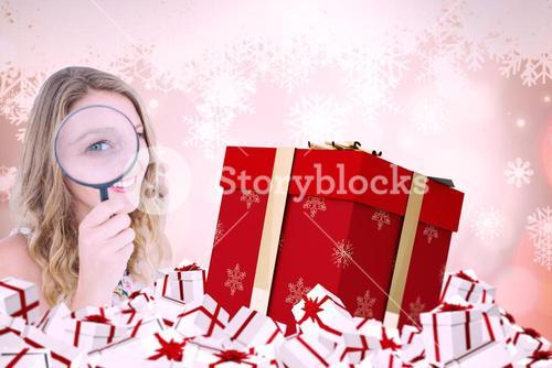 Composite image of smiling woman holding magnifying glass