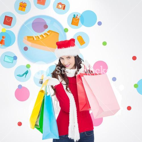 Composite image of smiling brunette in winter wear holding shopping bags