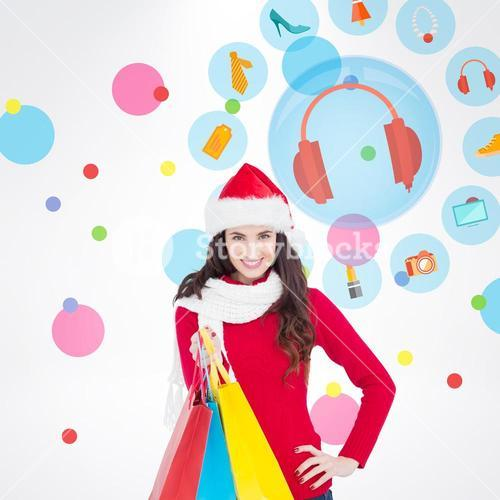 Composite image of brunette in winter clothes holding shopping bags