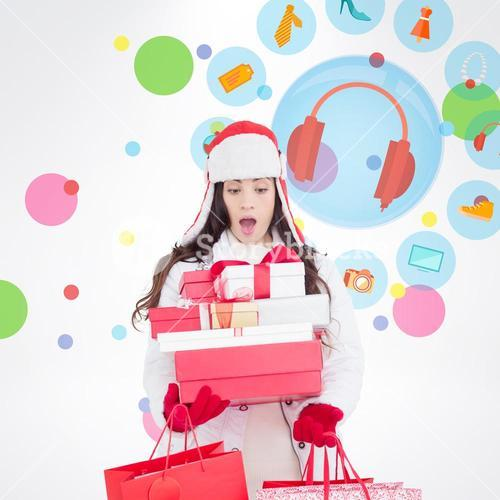 Composite image of surprised brunette in winter clothes holding many gifts and shopping bags