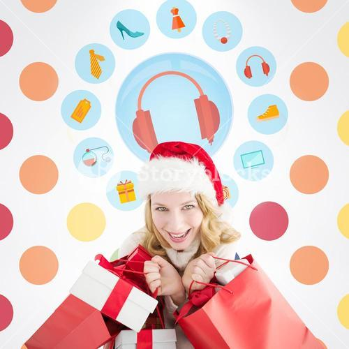 Composite image of girl in winter fashion holding presents and shopping bags