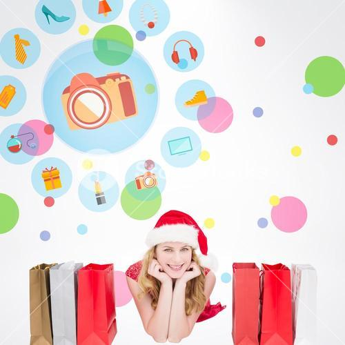 Composite image of smiling woman lying between shopping bags
