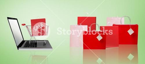 Composite image of trolley on laptop with sale bag
