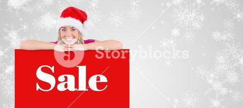 Composite image of festive blonde leaning on large poster