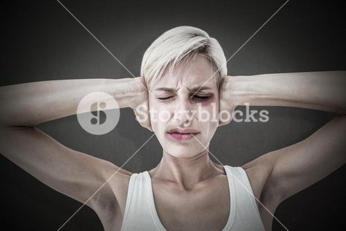 Composite image of upset woman covering her ears
