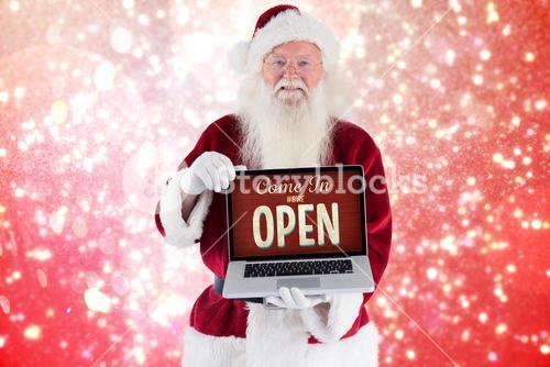 Composite image of santa claus presents a laptop