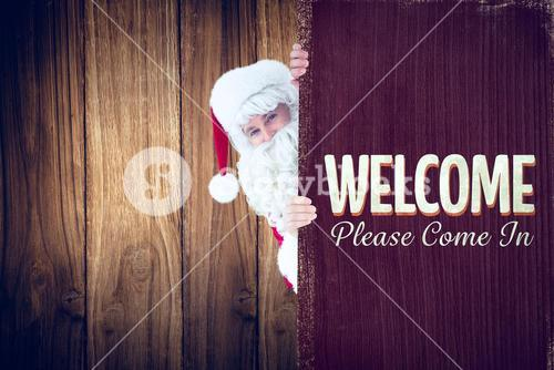 Composite image of smiling santa claus presenting sign