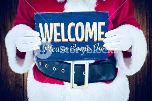 Composite image of mid section of santa claus holding page
