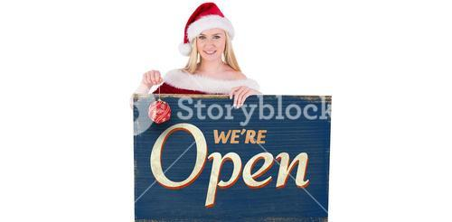 Composite image of festive cute blonde holding poster and bauble